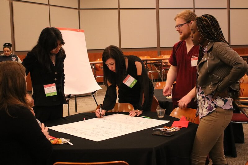 HEALTH Research Institute staff and pre-conference event attendees collaborating on the workshop group activity.