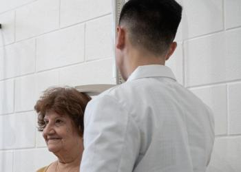 photo of woman getting her BMI measured at health fair