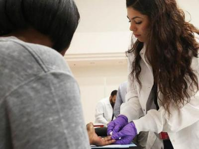researcher takes blood at health fair